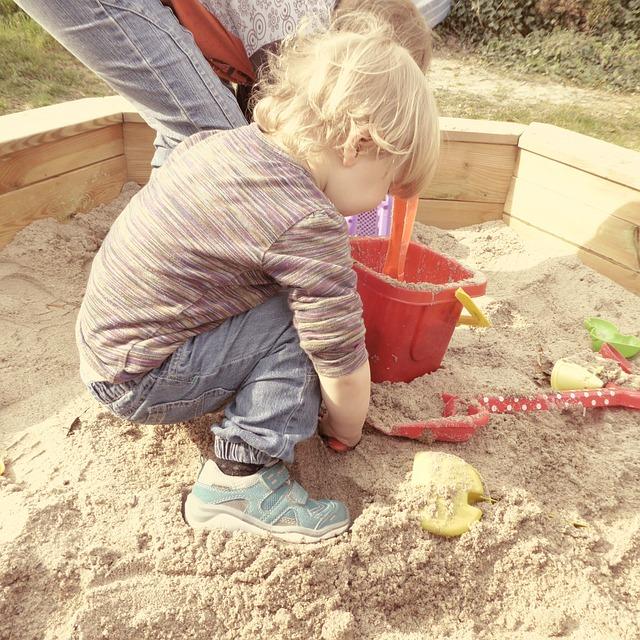 Kind spielt im Sandkasten mit Dach